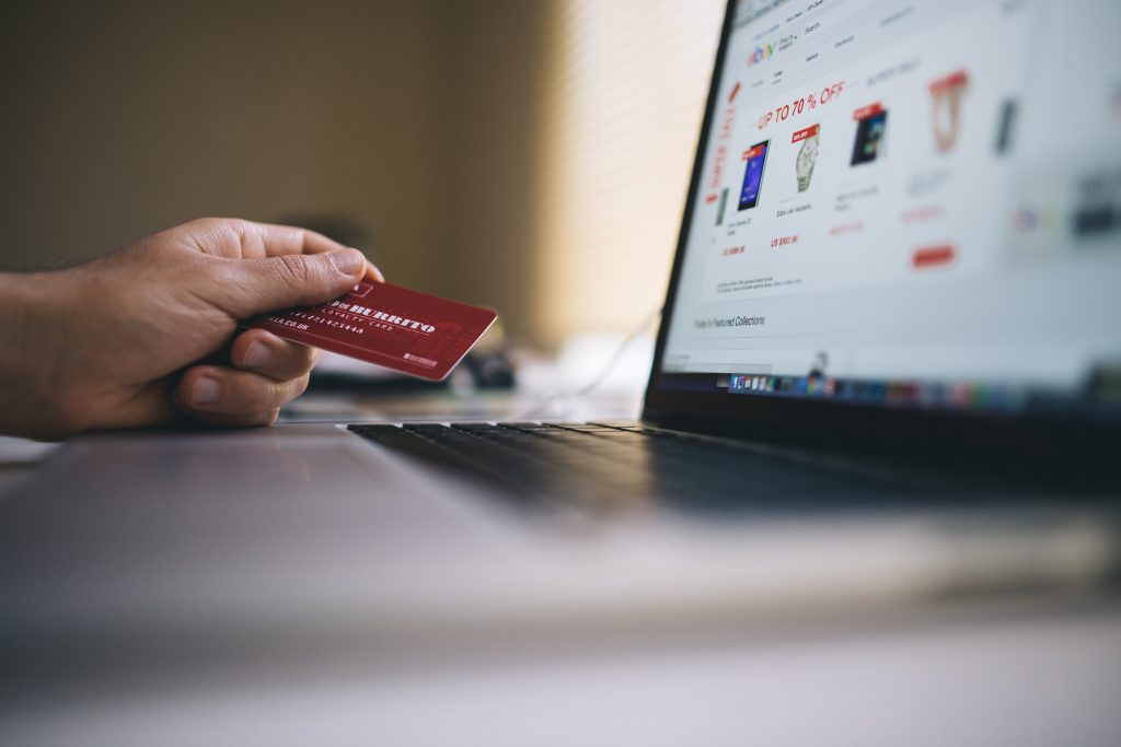 Person with credit card in hand looking at retail goods on laptop